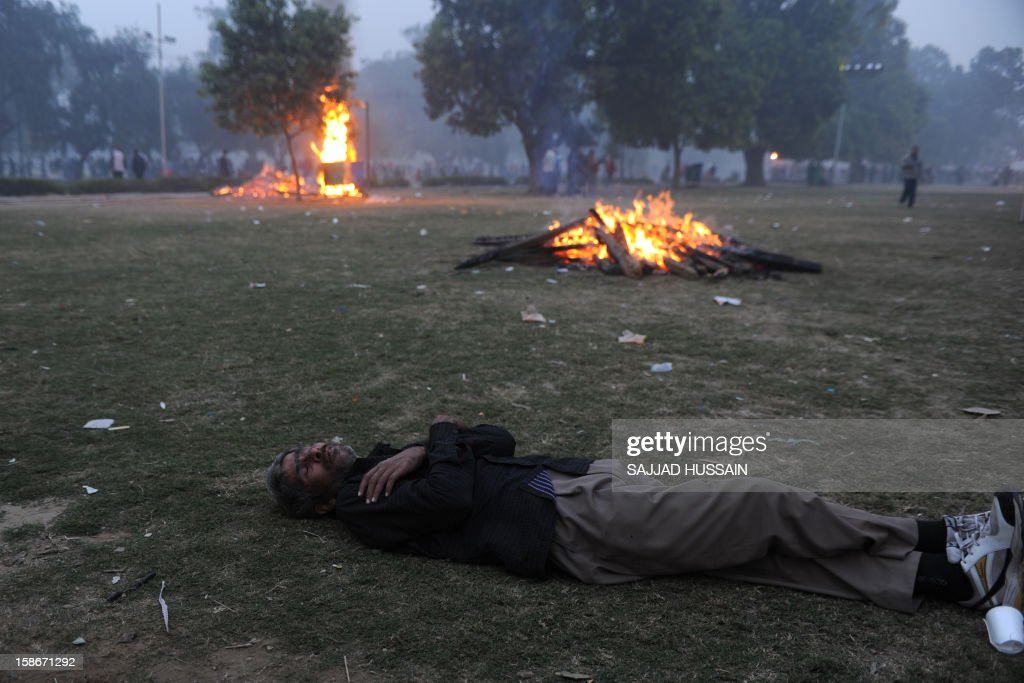 An injured demonstrator lies on the ground next burning barricades during a protest calling for better safety for women following the rape of a student last week, in front the India Gate monument in New Delhi on December 23, 2012. In the biggest protest so far, several thousand college students rallied at the India Gate monument in the heart of the capital where they were baton-charged, water cannoned and tear gassed by the police. AFP PHOTO/SAJJAD HUSSAIN