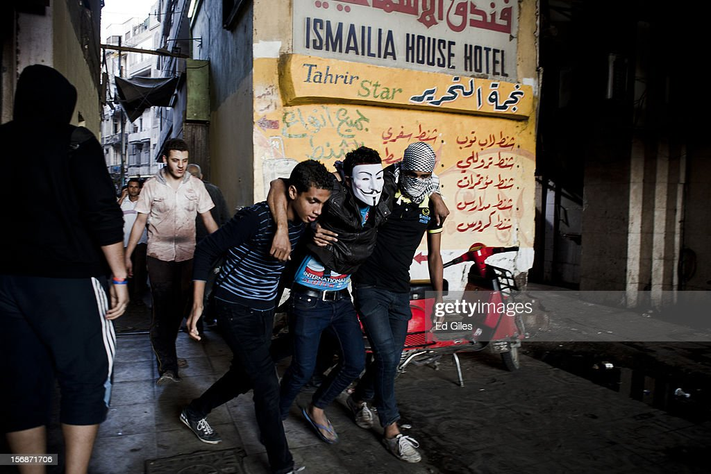 An injured Egyptian protester is helped away from violent clashes between riot police and demonstrators near Tahrir Square, on November 23, 2012 in Cairo, Egypt. Thousands of Egyptian protesters gathered in central Cairo's Tahrir Square on Friday to protest against a new constitutional declaration issued yesterday by Egyptian president Mohammed Morsi, giving him sweeping powers, and extending the period of deadline for the drafting of Egypt's new constitution by two months. The seven-article declaration renders the president's decrees and laws immune from appeal or cancellation. It also protects both Egypt's Shura Council and Islamist-dominated Constituent Assembly from dissolution by the country's judicial authorities. The demonstration follows a week of violent protests in central Cairo, commemorating one year since a series of deadly protests named 'Mohammed Mahmoud', after the street they took place in, during November 2011.