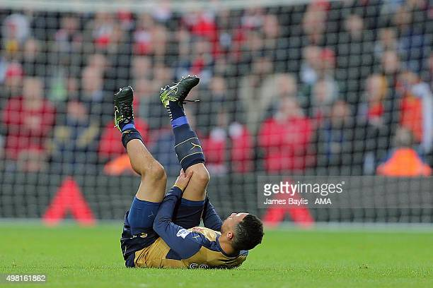 An injured Francis Coquelin of Arsenal holds his leg during the Barclays Premier League match between West Bromwich Albion and Arsenal at The...