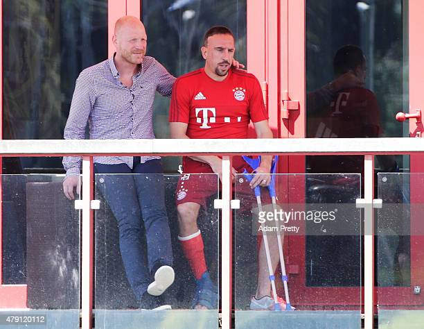 An injured Franck Ribery of FC Bayern Muenchen watches training with FC Bayern Sporting Director Matthias Sammer at the FC Bayern Muenchen training...