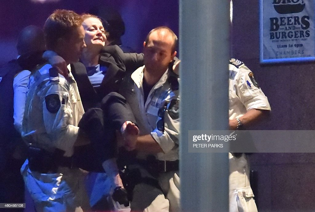 An injured hostage is carried out of a cafe in the central business district of Sydney on December 16 2014 Police stormed the Sydney cafe where a...