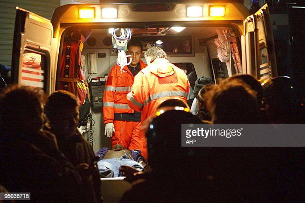 An injured immigrant worker lays on a stretcher in an ambulance after being injured during scuffles with Italian police late on January 7 2010 in the...