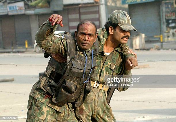 An injured Indian Center Reserve Police Force soldier is assisted during a shoot out in Lal Chowk in Srinagar 14 November 2005 Indian police...