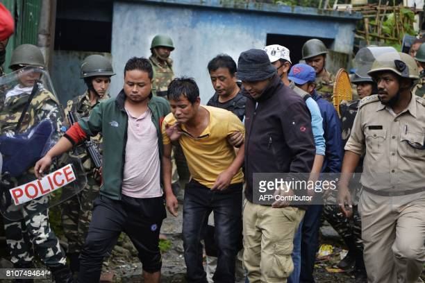 An injured Indian man is taken away during clashes between Gorkhaland supporters and the police during an indefinite strike called Gorkha Janamukti...