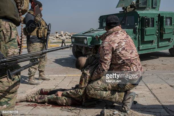 An injured Iraqi Emergency Response Division soldier hit by a mortar is held by another officer as they wait for medics to arrive at the Islamic...