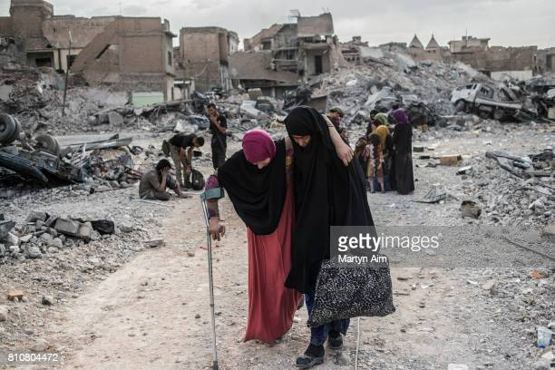 An injured Iraqi woman arrives at an Iraqi forces checkpoint in the occupied Old City district where heavy fighting continues on July 8 2017 in Mosul...