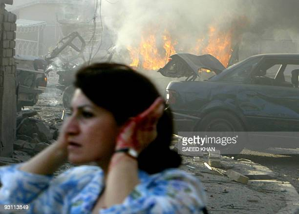 An injured Iraqi woman flees the site of two car bombs that exploded in quick succession near two Baghdad churches 01 August 2004 causing many...