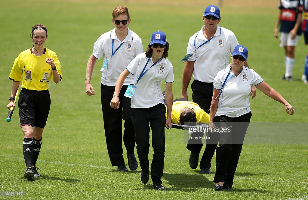 An injured lineswoman is carried off on a stretcher during the round 10 W-League match between the Newcastle Jets and Melbourne Victory at Adamstown Oval on January 25, 2014 in Newcastle, Australia.