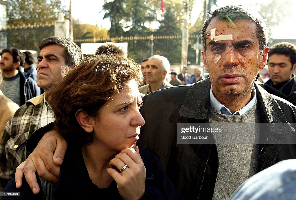 An injured man and his wife revisit the scene of the British Consulate bombing November 21, 2003 in Istanbul, Turkey. Bomb attacks on the British consulate and the HSBC bank headquarters on November 20, 2003 killed at least 27 people and left hundreds injured.