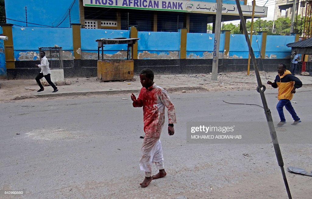 An injured man covered with blood runs away from the scene of a car bomb attack claimed by Al-Qaeda-affiliated Shabaab militants, which killed at least 5 people, on the Naasa Hablood hotel in Mogadishu on June 25, 2016. The hotel in southern Mogadishu is often used by politicians and members of the Somali diaspora visiting the city. The attack came just three weeks after another assault quickly claimed by the Al-Qaeda-linked Shabaab group on the city's Ambassador hotel left 10 dead including two lawmakers when a huge car bomb ripped the front off the six-storey building. / AFP / MOHAMED