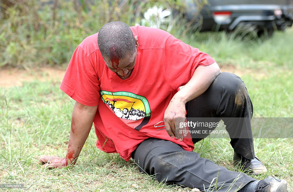 An injured man dressed in the red color of the Congress of South African Trade Unions (Cosatu) rests after being beaten up by striking miners and as South African police officers fire rubber bullets, stun grenades and tear gas to disperse miners who were trying to prevent a rally organised by the Congress of South African Trade Unions (Cosatu) in Rustenburg, northwest of Johannesburg on October 27, 2012. Bullet casings littered the ground and a helicopter circled above, with police sirens howling, as the protesters were chased into the area surrounding the stadium. The clashes came a day after the National Union of Mineworkers (NUM) announced that it had reached a deal with the world's number one platinum producer Amplats to rehire 12,000 workers who were fired for a wildcat strike. Striking workers are disagree with the deal, which would signal a further winding down of a wave of wildcat strikes that have rocked platinum and gold mines since August.