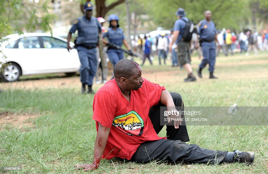 An injured man dressed in the red color of the Congress of South African Trade Unions (Cosatu) rests after being beaten up by striking miners and as South African police officers fire rubber bullets, stun grenades and tear gas to disperse miners who were trying to prevent a rally organised by the Congress of South African Trade Unions (Cosatu) in Rustenburg, northwest of Johannesburg on October 27, 2012. Bullet casings littered the ground and a helicopter circled above, with police sirens howling, as the protesters were chased into the area surrounding the stadium. The clashes came a day after the National Union of Mineworkers (NUM) announced that it had reached a deal with the world's number one platinum producer Amplats to rehire 12,000 workers who were fired for a wildcat strike. Striking workers are disagree with the deal, which would signal a further winding down of a wave of wildcat strikes that have rocked platinum and gold mines since August. AFP PHOTO / STEPHANE DE SAKUTIN
