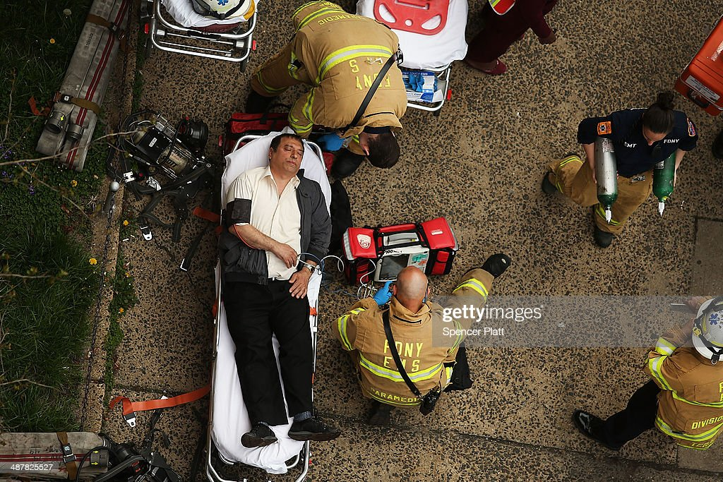 An injured man is aided by New York City firefighters after being evacuated from an emergency staircase following an F train derailment on May 2, 2014 in the Woodside neighborhood of the Queens borough in New York City. According to the Metropolitan Transportation Authority (MTA) the express F train was bound for Manhattan and Brooklyn when it derailed at 10:40 a.m. about 1,200 feet from the 65th station in Woodside, Queens with hundreds of passengers on board.