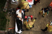 An injured man is aided by New York City firefighters after being evacuated from an emergency staircase following an F train derailment on May 2 2014...
