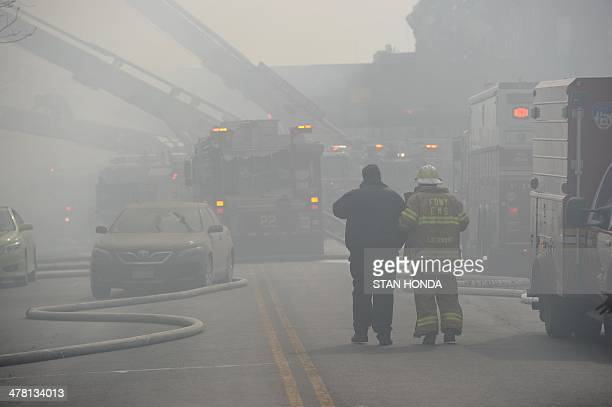 An injured man is assisted by NYFD emrgency medical services personell near the scene of an explosion and building collapse at Park Avenue and East...