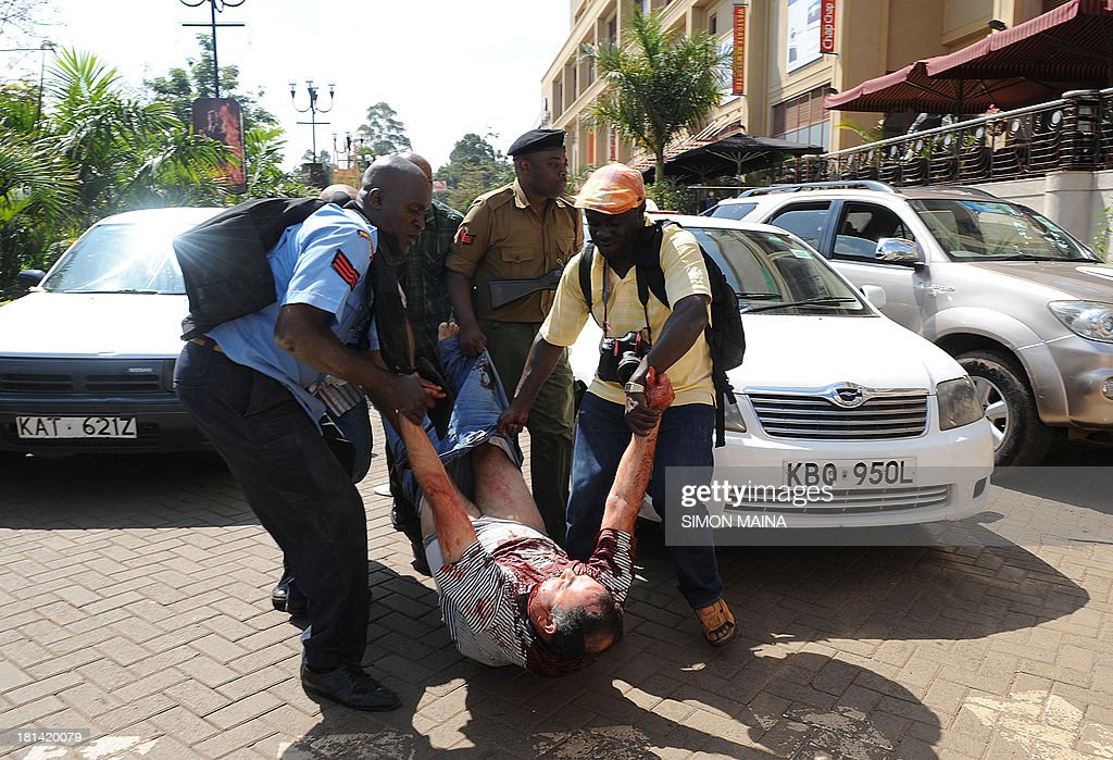 An injured man is carried away after masked gunmen stormed an upmarket mall and sprayed gunfire on shoppers and staff, killing at least six on September 21, 2013 in Nairobi. The Gunmen have taken at least seven hostages, police and security guards told an AFP reporter at the scene.