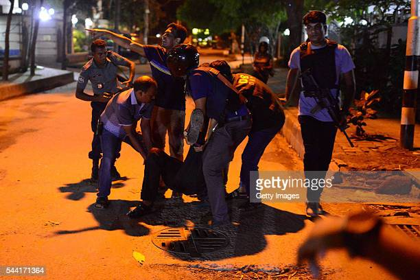 An injured man receieves help after an attack at a restaurant in the early hours of July 2 2016 in Dhaka Bangladesh Gunmen have taken at least 20...