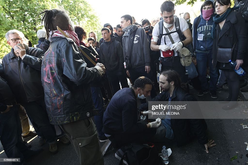 An injured man receives first aid following clashes between French anti riot police and protesters during the traditional May Day demonstration in Paris on May 1, 2016.
