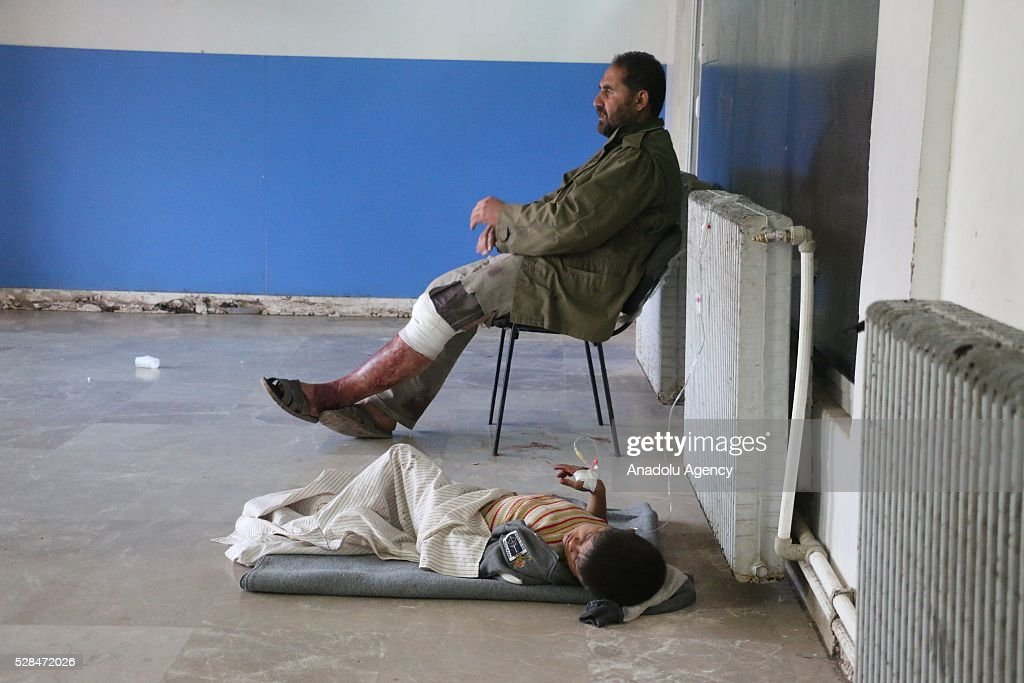 An injured man sits on a chair and a kid lies on the floor as they receive medical treatment at a field hospital after a Syrian regime warplane targeted the Kamuna refugee camp near the Syrian town of Sarmada town in the Idlib province after Syrian regime warplane targeted the camp on May 05, 2016. Eight people were killed and another 30 injured when a regime warplane targeted the Kamuna refugee camp.