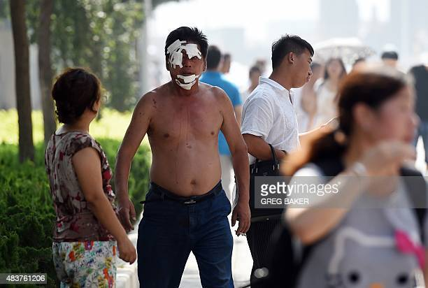 An injured man walks out with other residents from an area near the site of a series of explosions in Tianjin northern China on August 13 2015 A...