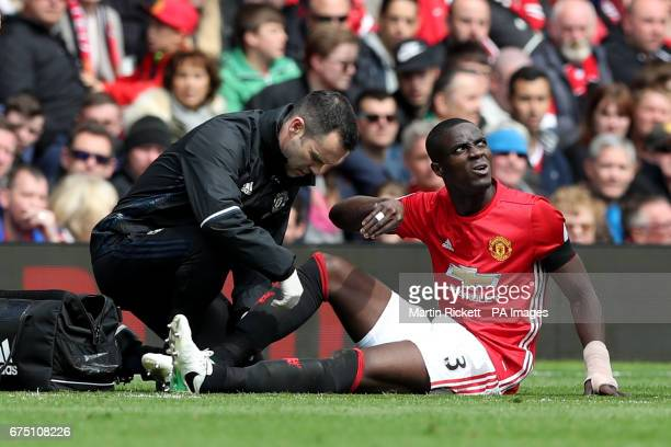 An injured Manchester United's Eric Bailly is treated on the pitch during the Premier League match at Old Trafford Manchester