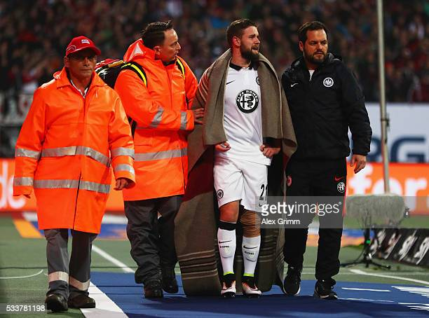 An injured Marc Stendera of Eintracht Frankfurt is given assistance during the Bundesliga Playoff final second leg match between 1 FC Nuernberg and...