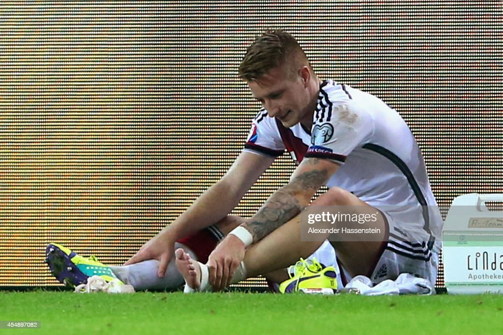 An injured <a gi-track='captionPersonalityLinkClicked' href=/galleries/search?phrase=Marco+Reus&family=editorial&specificpeople=5445884 ng-click='$event.stopPropagation()'>Marco Reus</a> of Germany is given treatment during the EURO 2016 Group D qualifying match between Germany and Scotland at Signal Iduna Park on September 7, 2014 in Dortmund, Germany.