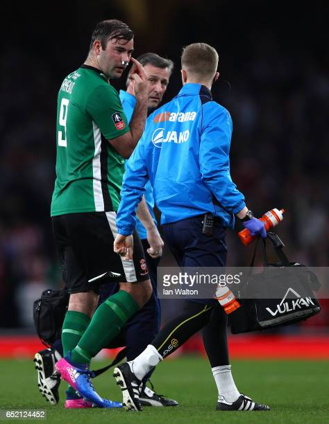 An injured Matt Rhead of Lincoln City is given assistance during The Emirates FA Cup QuarterFinal match between Arsenal and Lincoln City at Emirates...