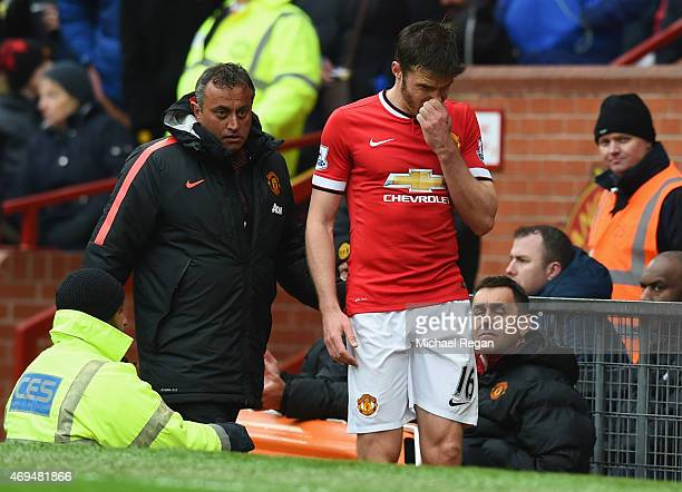 An injured Michael Carrick of Manchester United walks along the touchline the Barclays Premier League match between Manchester United and Manchester...