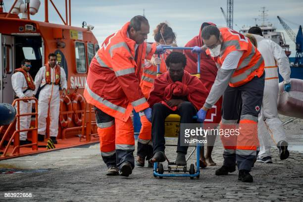 An injured migrant in a wheelchair being helped by the Spanish Red cross after arriving on a Spanish coast guard vessel into the southern Spanish...