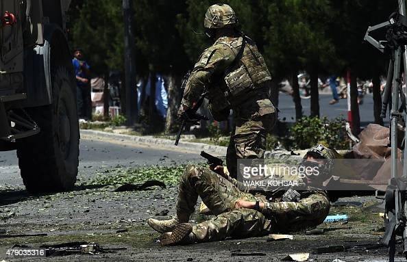 An injured NATO soldier lies on the ground following a suicide car bomb attack that targeted foreign military vehicles in the Afghan capital Kabul on...