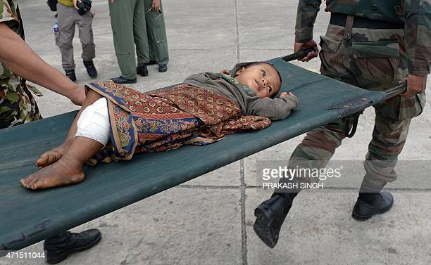 An injured Nepalese boy is carried to a field hospital at an airport in Kathmandu on April 29 2015 Desperate people in Nepal clashed with riot police...