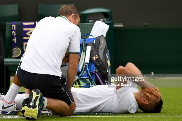 An injured Nick Kyrgios of Australia is given treatment during the Gentlemen's Singles first round match against PierreHugues Herbert of France on...