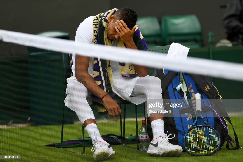 An injured Nick Kyrgios of Australia reacts as he retires during the Gentlemen's Singles first round match against Pierre-Hugues Herbert of France on day one of the Wimbledon Lawn Tennis Championships at the All England Lawn Tennis and Croquet Club on July 3, 2017 in London, England.