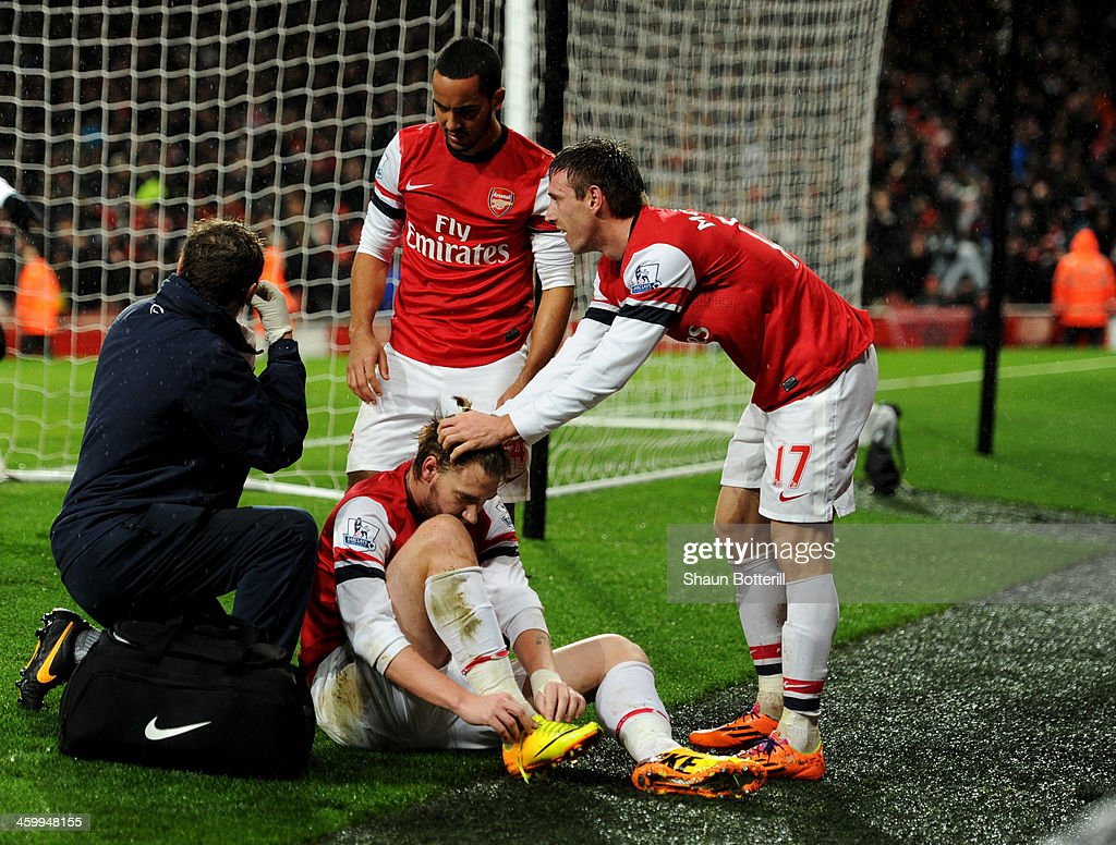 An injured Nicklas Bendtner of Arsenal is congratulated by team mates Theo Walcott and Nacho Monreal as he scores their first goal during the...