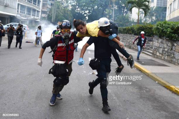 TOPSHOT An injured opposition activist is taken away by volunteer medics during protest against the government of President Nicolas Maduro at the...