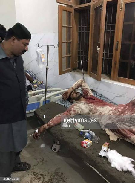 An injured Pakistani blast victim is treated at a local hospital after a bomb explosion in the shrine of 13th century Muslim Sufi saint Lal Shahbaz...