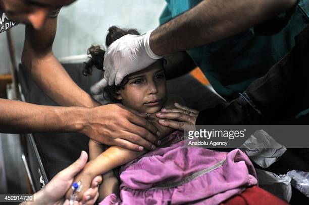 An injured Palestinian kid receives treatment at Kamal Adwan hospital in Beit Lahia Gaza on July 30 2014 The death toll from the Israeli shelling of...