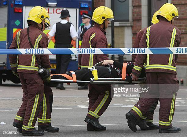 An injured passenger is carried by fire brigade officers after evacuation from Mile End station on July 5 2007 in London Up to six carraiges of a...