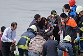 An injured passenger is helped onto land by emergency personnel along the river bank after a TransAsia ATR 72600 turboprop plane crashlanded into the...