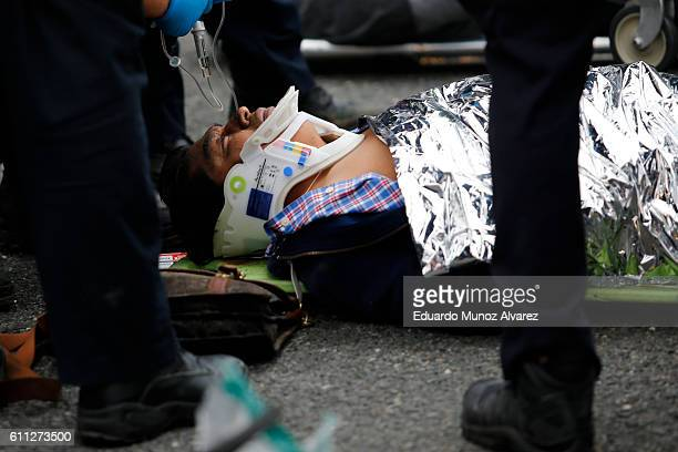 An injured passenger is treated after a New Jersey Transit train crashed into the platform at Hoboken Terminal during morning rush hour September 29...