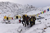 An injured person is carried by rescue members to be airlifted by rescue helicopter at Everest Base Camp on April 26 a day after an avalanche...