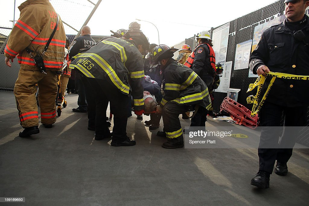 An injured person is carried to a waiting ambulance following an early morning ferry accident during rush hour in Lower Manhattan on January 9, 2013 in New York City. About 50 people were injured in the accident, which left a large gash on the front side of the Seastreak ferry at Pier 11.