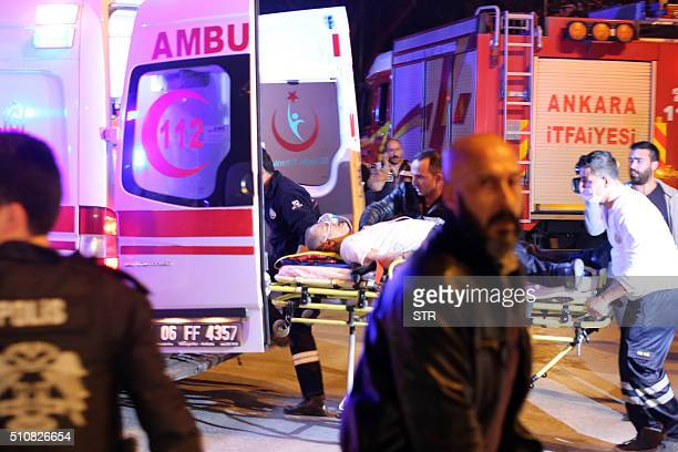 An injured person is loaded into an ambulance car following an explosion after an attack targeted a convoy of military service vehicles in Ankara on...