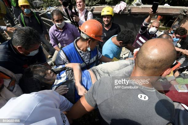 An injured person is taken away on a stretcher after being rescued from the ruins of a collapsed building after a quake in Mexico City on September...