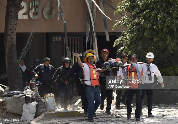 An injured person is taken away on a stretcher by rescuers after a powerful quake in Mexico City on September 19 2017 A powerful earthquake shook...