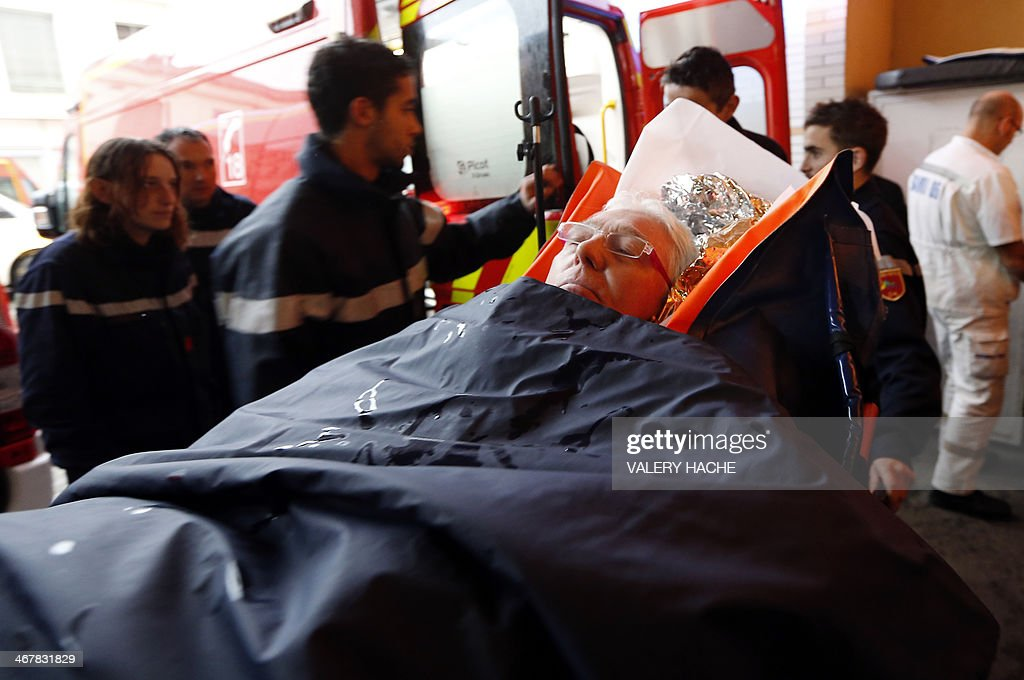 An injured person, laying on a stretcher, arrives at the hospital of Nice, southern France, after a train derailed near Digne-les-Bains in the French Alps on February 8, 2014. Two women were killed when a massive falling boulder hit a passing train in the French Alps on Saturday, leaving one of its carriages dangling precariously off a steep, snow-covered embankment. Eight people were injured in the accident which took place as the train travelled from the coastal city of Nice to the popular tourist town of Digne-les-Bains along a narrow, winding, and sometimes breathtakingly steep track. AFP PHOTO / VALERY HACHE