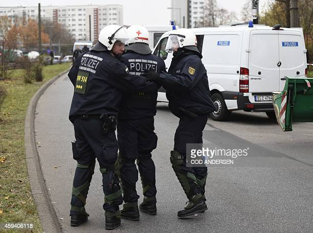 An injured policeman is accompanied by colleagues after he clashed with the participant of counterdemonstrator while people demonstrate against the...