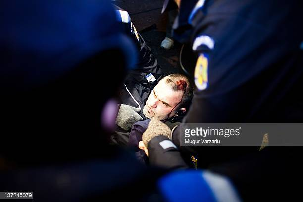 An injured policeman is aided by colleagues during clashes with protesters opposed to austerity measures imposed by the government clashed with riot...