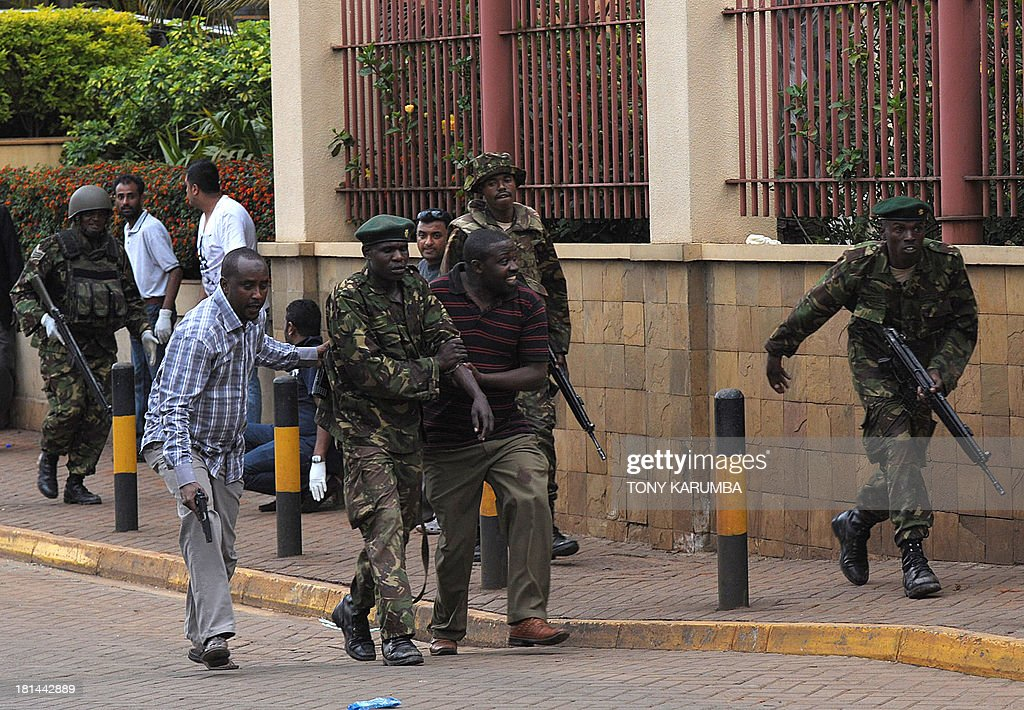 An injured policeman is evacuated by his colleagues on September 21, 2013 after he was shot during a security operation at an upmarket shopping mall in Nairobi where suspected terrorrists engaged Kenyan security forces in a drawn out gun fight. Some 20 people have been killed and about 50 wounded Saturday in the initial attack by the gunmen the Kenya Red Cross said. AFP PHOTO / Tony KARUMBA